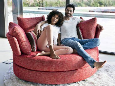 Cette loveuse duo, disponible en base pivotante ou sur pieds, se décline en cuir et en tissu. Elle existe dans de nombreux coloris