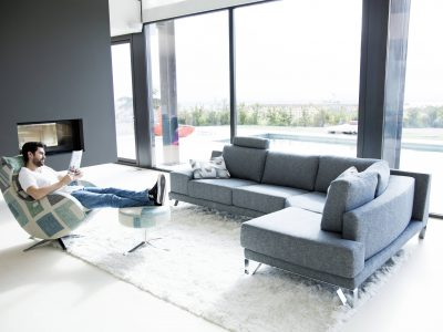 Canapé avec accoudoir amovible, qui peut être posé au sol pour se transformer en repose pied, et qui existe dans de nombreuses configurations.