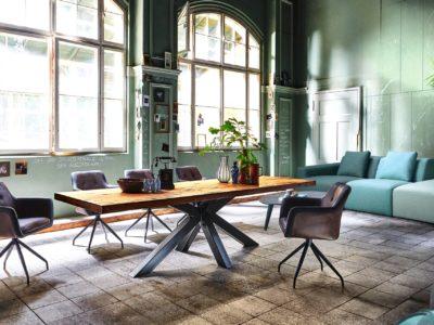 La table chêne rustique et pied métal, au design industriel, présente un piétement original.